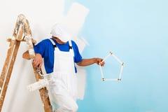 Pintor con el paintroller que muestra una casa del criterio Fotografía de archivo libre de regalías
