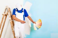 Pintor con el paintroller que muestra una paleta de colores Foto de archivo libre de regalías