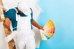 Pintor con el paintroller que muestra una paleta de colores Imágenes de archivo libres de regalías