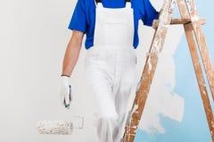 Pintor con el rodillo de pintura en escalera Fotografía de archivo