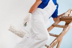 Pintor con el rodillo de pintura en escalera Foto de archivo libre de regalías