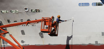 Pintor con un casco de la capa del rodillo de pintura de una nave Imagenes de archivo