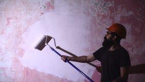 Pintor con una poder y cepillo en su sitio de trabajo El hombre del pintor en el trabajo toma el color con la brocha del rodillo metrajes