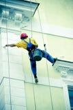 Pintor da fachada em cordas do abseil Foto de Stock Royalty Free