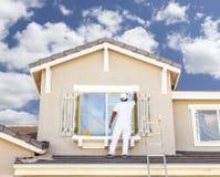 Pintor de casa profissional Painting a guarnição e os obturadores da casa Foto de Stock
