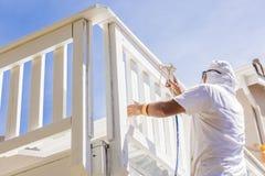 Pintor de casa profissional Spray Painting uma plataforma de uma casa Foto de Stock Royalty Free