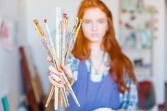 Pintor de la mujer joven que muestra las brochas sucias en taller del artista Foto de archivo