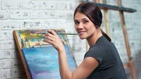Pintor de sexo femenino atractivo que presenta en la brocha de la tenencia del taller durante imagen de dibujo metrajes