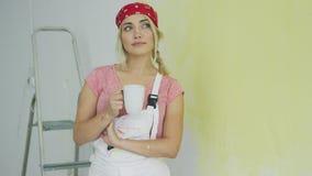 Pintor de sexo femenino en los guardapolvos que descansan con la bebida almacen de video