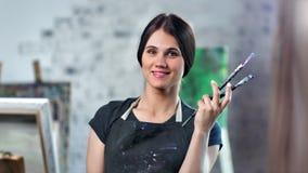 Pintor de sexo femenino feliz del retrato medio del primer que presenta sosteniendo el cepillo profesional del arte almacen de metraje de vídeo