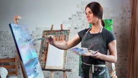 Pintor de sexo femenino hermoso sonriente que disfruta del trabajo en el tiro medio del estudio del arte almacen de metraje de vídeo