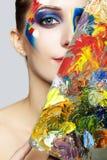 Pintor de sexo femenino joven con la paleta de colores y la pintura acrílica en el fa foto de archivo