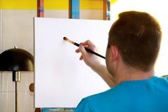 Pintor de sexo masculino del artista que trabaja en taller con la lona en el caballete de madera del tablero de dibujo en estudio fotos de archivo