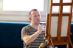 Pintor de sexo masculino del artista que trabaja en taller con la lona en el caballete de madera del tablero de dibujo en estudio imágenes de archivo libres de regalías