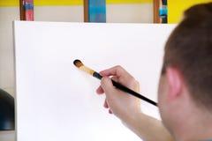 Pintor de sexo masculino del artista que trabaja en taller con la lona en el caballete de madera del tablero de dibujo en estudio fotos de archivo libres de regalías