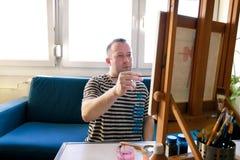Pintor de sexo masculino del artista que trabaja en taller con la lona en el caballete de madera del tablero de dibujo en estudio foto de archivo