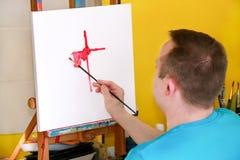 Pintor de sexo masculino del artista que trabaja en taller con la lona en el caballete de madera del tablero de dibujo en estudio imagenes de archivo