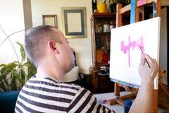 Pintor de sexo masculino del artista que trabaja en taller con la lona en el caballete de madera del tablero de dibujo en estudio foto de archivo libre de regalías