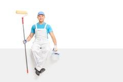 Pintor de sexo masculino que sostiene un rodillo de pintura asentado en el panel imagen de archivo libre de regalías