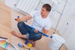 Pintor de Youg que se sienta en el piso que lleva a cabo el paintroller Imagenes de archivo