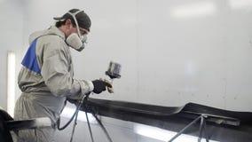 Pintor del coche que rocía la pintura negra en pieza de carrocería metrajes