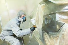 Pintor del reparador en capo del coche del automóvil de la pintura de la cámara foto de archivo libre de regalías