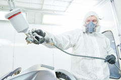 Pintor do reparador na capota do carro do automóvel da pintura da câmara foto de stock