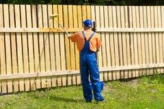 Pintor em brins azuis que decora a cerca de madeira Fotos de Stock