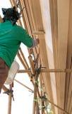 Pintor en el andamio de madera que pinta la casa exterior imágenes de archivo libres de regalías