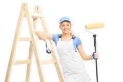 Pintor fêmea novo que guarda um rolo de pintura Fotos de Stock Royalty Free