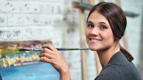 Pintor feliz de la mujer que presenta sosteniendo la brocha con la pintura del color que mira el primer de la c?mara metrajes