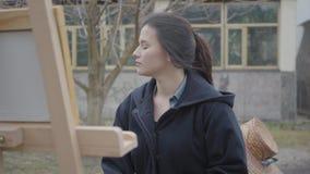 Pintor hermoso acertado de la chica joven que se sienta delante del caballete de madera que mira alrededor r metrajes