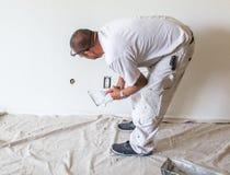 Pintor hispánico que pone el spackle en una pared imagen de archivo libre de regalías