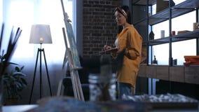 Pintor joven que dibuja los detalles finales de las ilustraciones almacen de metraje de vídeo