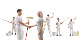 Pintor masculino que agita as mãos com uma jovem mulher e os trabalhadores que pintam a parede imagens de stock
