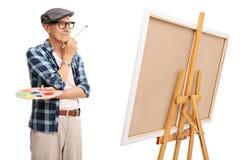 Pintor mayor que mira una pintura Fotos de archivo libres de regalías