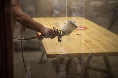 Pintor mestre em uma fábrica - madeira industrial da pintura com arma de pulverizador Foco macio fotos de stock