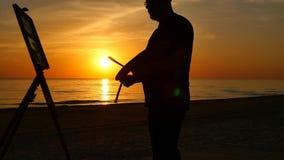 Pintor miking un primer de la imagen en la cámara lenta de la silueta de la puesta del sol metrajes