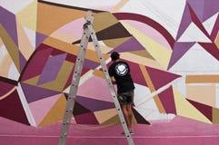 Pintor na parede dos grafittis com associação do epistrophe Fotografia de Stock