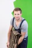 Pintor novo considerável que leva uma escada portátil Imagens de Stock Royalty Free