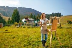 Pintor novo no trabalho nas montanhas Fotos de Stock Royalty Free