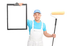 Pintor novo que guarda o rolo de pintura e uma prancheta Imagem de Stock Royalty Free