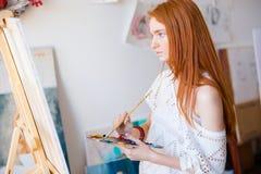 Pintor pensativo concentrado da mulher com pintura longa do cabelo na lona fotos de stock