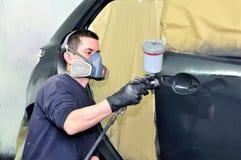Pintor profesional del coche que trabaja en un vehículo Imagenes de archivo