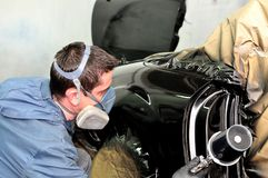 Pintor profesional del coche que trabaja en un vehículo Fotografía de archivo libre de regalías