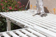 Pintor profesional Rolling White Paint sobre el top de un hogar Imagen de archivo libre de regalías