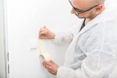 Pintor profissional que cola a fita perto do interruptor foto de stock royalty free