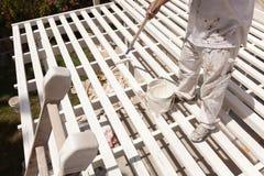 Pintor profissional Rolling White Paint na parte superior de uma casa fotos de stock