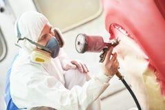 Pintor que pinta un coche rojo Imagen de archivo libre de regalías