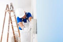 Pintor que pinta una pared con el rodillo de pintura Fotografía de archivo